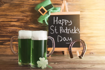 Mugs of green beer for St. Patrick's Day on wooden table