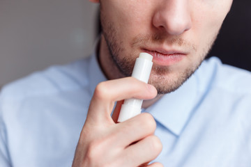 Man applying hygienic lipstick on lips to revive chapped lips and avoid dry, closeup Papier Peint