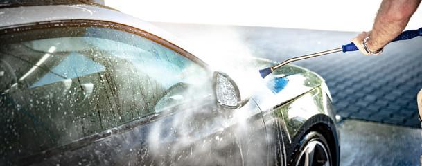 Mann putzt den Spiegel seines Auto an einer Waschstation