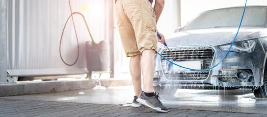 Mann putzt sein Auto an einer Waschstation Fototapete