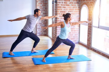 Middle age beautiful sporty couple smiling happy. Standing with smile on face practicing yoga doing...