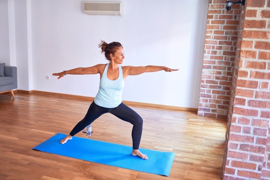 Middle age beautiful sportwoman standing on mat. Practicing yoga doing warrior pose at gym
