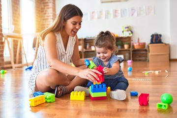 Young beautiful teacher and toddler playing with building blocks toy at kindergarten