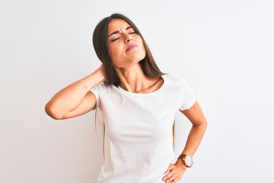 Young beautiful woman wearing casual t-shirt standing over isolated white background Suffering of neck ache injury, touching neck with hand, muscular pain