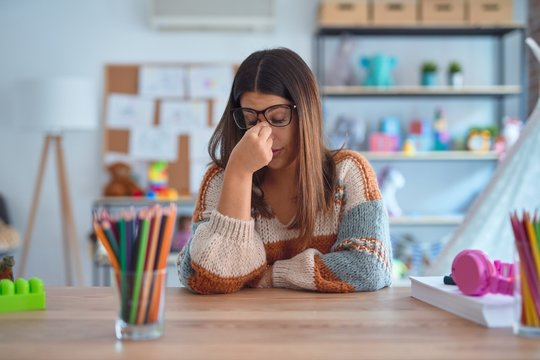 Young beautiful teacher woman wearing sweater and glasses sitting on desk at kindergarten tired rubbing nose and eyes feeling fatigue and headache. Stress and frustration concept.