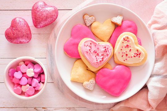 Heart shaped Valentines Day cookies with pink and white icing and sprinkles. Top view table scene against a white wood background.