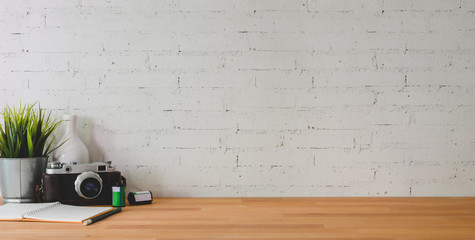 Wall Mural - Cropped shot of comfortable workplace with camera and office supplies on wooden table and brick wall