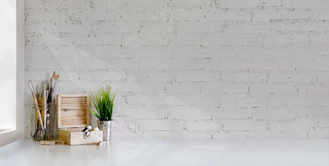 Wall Mural - Cropped shot of minimal artist workplace with painting tools on white table and white brick wall
