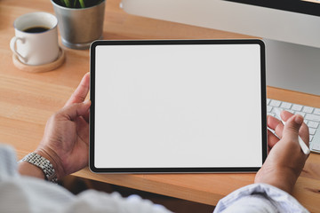 Cropped shot of young man holding blank screen digital tablet