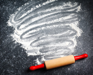 Rolling pin and white flour on a dark background. Copy space for text. Top view.