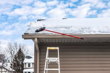 Gutters with ice dam and broom for raking snow off of roof
