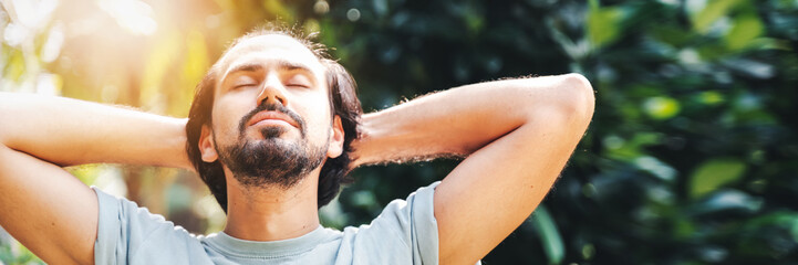 A bearded man is meditating outdoor in the park with face raised up to sky and eyes closed on sunny summer day. Concept of meditation, dreaming, wellbeing healthy lifestyle