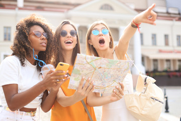 Holidays and tourism concept - beautiful girls looking for direction in the city. Fotomurales