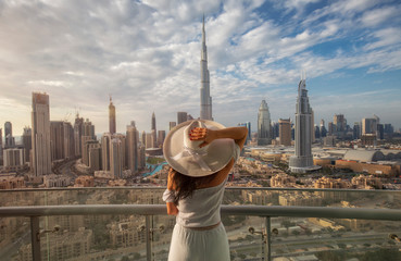 Spoed Fotobehang Dubai Woman with a white hat is standing on a balcony in front of the skyline from Dubai Downtown