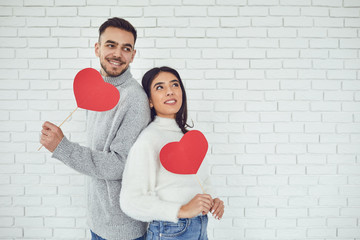 Concert Valentine's Day. Young couple with hearts in hands on a white brick background