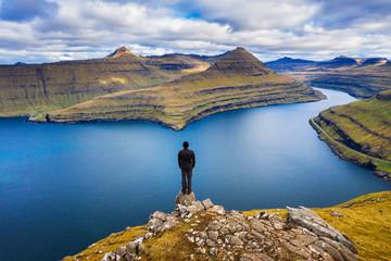 Wall Mural - Hiker enjoys views over fjords from a mountain near Funningur on Faroe Islands