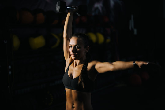 Sexy strong muscular female with perfect muscular body in black sportswear is lifting kettlebell overhead during weight training workout. Concept of healthy lifestyle and workouts in a modern dark gym