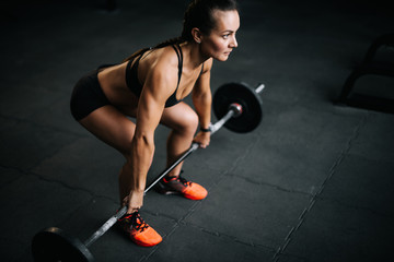 Strong woman bodybuilder with perfect fitness body preparing to lift the heavy barbell from the floor. Concept of healthy lifestyle and workouts in a modern dark gym.