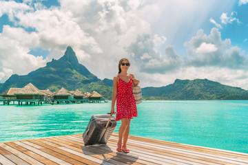 Hotel luxury resort tourist woman arriving with luggage suitcase in Tahiti Bora Bora honeymoon...