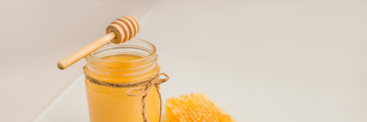 Foto op Aluminium Europa Honey pot with honey dipper and natural honeycomb banner background.