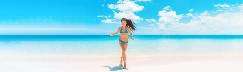 Beach Asian woman with fit summer bikini body happy running enjoying Caribbean vacation laughing of joy in tropical destination banner panorama. Blue swimwear model enjoying summer holidays.