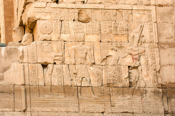 Karnak temple complex in Luxor, Egypt. Ancient bas relief with hieroglyphs on wall, pharaoh and god.