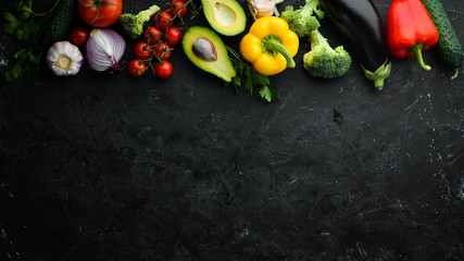 Fotomurales - Ripe vegetables. Fresh vegetables on black stone background. Tropical fruits. Top view. Free space for your text.