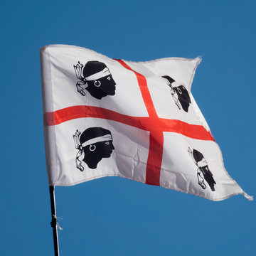 Traditional flag of the Sardinian  island, that is white with a red cross and a black moor's head, with a white headband, above the eyes.