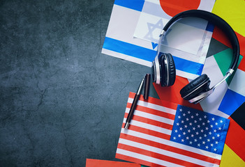 Learning foreign languages. Audio language courses. Background from countries flags and headphones...