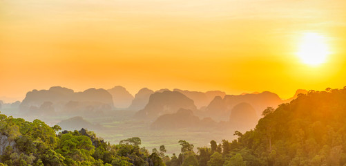 Beautiful panorama landscape with dramatic sunset, tropical rainforest and steep mountain ridge on horizon. Krabi, Thailand
