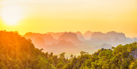 Foto op Plexiglas Oranje Beautiful panorama landscape with dramatic sunset, tropical rainforest and steep mountain ridge on horizon. Krabi, Thailand