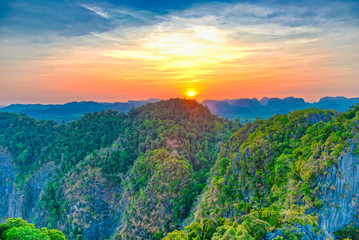 Majestic landscape with dramatic sunset and silhouette of steep mountain ridge on horizon. HDR image