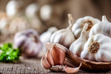 Garlic clove and bulbs in wooden bowl. Fresh garlics head on jute. Wall mural