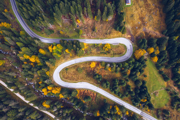Curved bending road in the forest. Aerial image of a road. Forrest pattern. Scenic curvy road seen from a drone in autumn. Aerial top down view of zig zag winding mountain road, drone shot.