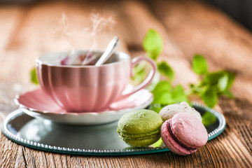 Foto auf Leinwand Macarons Sweet cake macarons and green tea. Colorful macarons with tea and mint on wooden table.