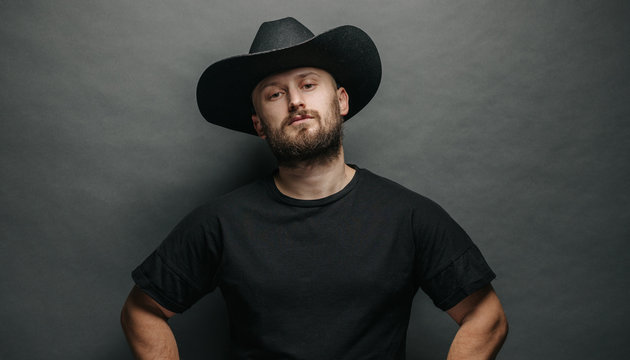 Handsome cowboy wearing black cowboy hat with beard