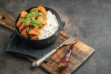 Chicken tikka masala traditional Asian spicy meat food with rice tomatoes and cilantro in a black bowl on dark background.
