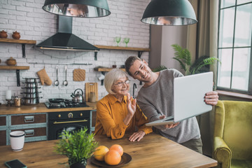 Young handsome man in grey shirt and his mom talking online with friends Wall mural