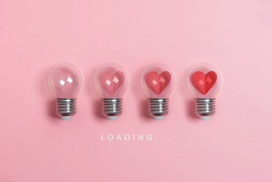 Red hearts in light bulbs. Loading progress bar on pink background. Valentine's day, Creative idea, Love, Inspiration Concepts.