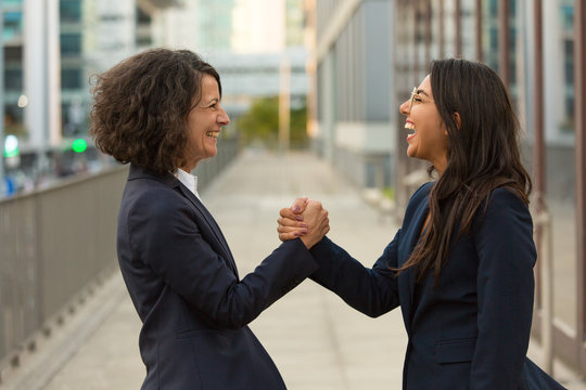 Happy excited colleagues celebrating triumph together. Business women giving friendly handshake outside. Teamwork and success concept