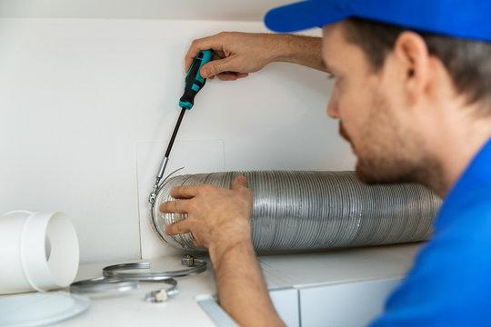 worker installing flexible aluminum ventilation tube for kitchen cooker hood exhaust system