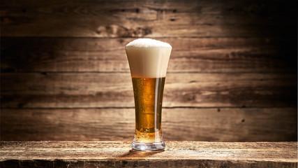 Szklanka pełna piwa zpianą na tle starych desek