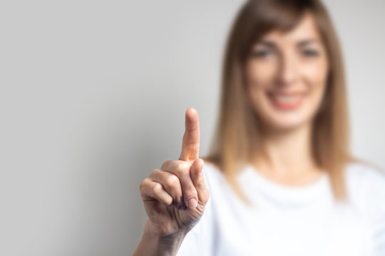 Young woman touches or pushes a finger at something on a light background