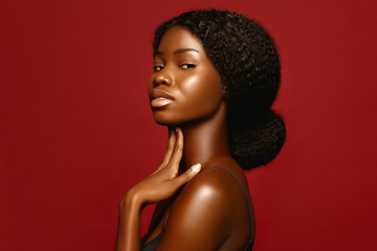 Fashion Beauty African American beautiful woman profile portrait. Brunette curly haired young model with dark skin  against red background