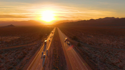 Photo sur Aluminium Marron chocolat DRONE: Scenic shot of 18 wheeler trucks and cars crossing Mojave desert at dusk