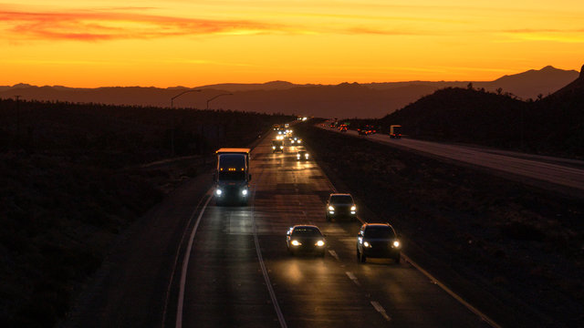 AERIAL: Commuters and truckers drive down the Mojave freeway at scenic twilight.