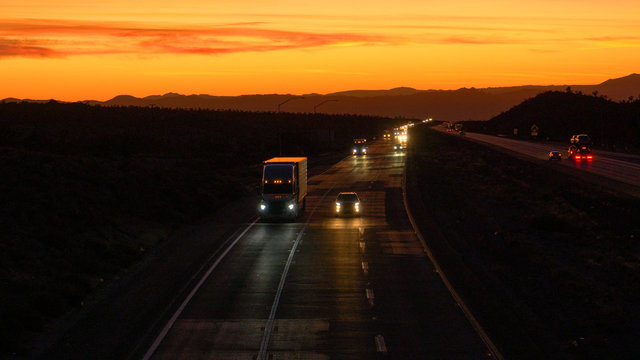 DRONE: Commuters and truckers drive down the Mojave freeway at scenic twilight.