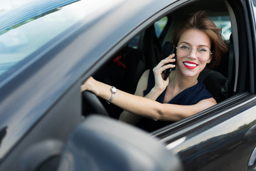 business woman with red lips in a classic suit sitting on the driver's seat in the car and talking...