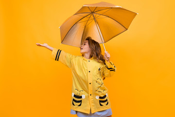 Foto op Textielframe Bee happy joyful girl in a beautiful yellow raincoat in the image of a bee holds a silver umbrella and extends her hand on a yellow background