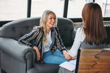 Obraz Young successful women colleagues talk to each other, coaching or psychotherapy in modern loft office - fototapety do salonu